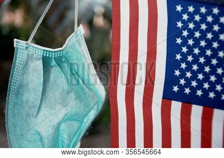 Focus On Some Points Of Surgery Mask Hanging With United State Flag. Health Mask. Used To Prevent Co