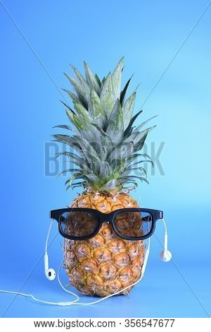 Pineapple In Sunglasses And Heardpods Close-up On Blue Background