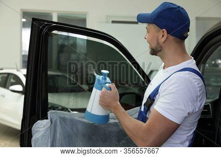 Worker Spraying Water Onto Tinted Car Window In Workshop