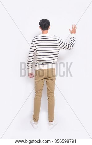 full length young man isolated on white background wearing striped  sweater and khaki pants full body, full length
