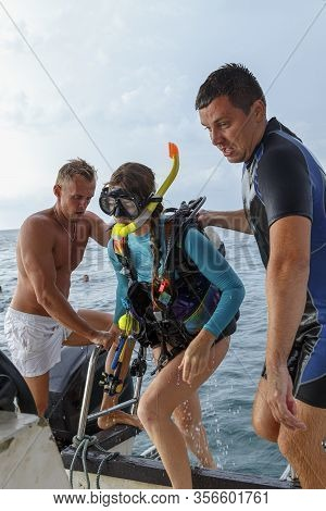 Team Of Young Divers, Young Men Help A Young Girl Diver Get On Board Boat