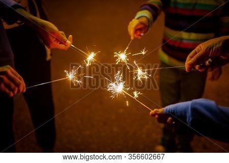 Group Hands Holding Burning Sparking Stick Starlight Fireworks Pyrotechnic Warm Dark Background Cele