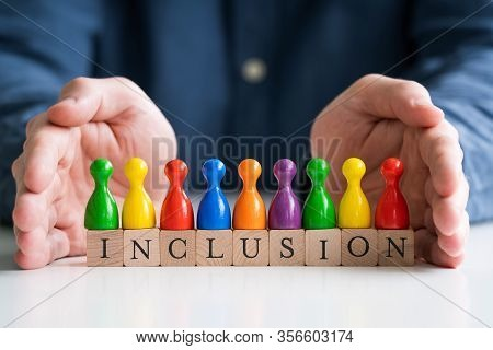 Man Protecting Inclusion Text And Multi Colored Pawns