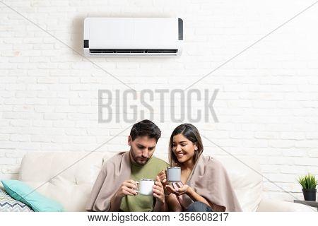 Hispanic Heterosexual Couple Covered In Blankets Having Coffee Below Mini Split At Home