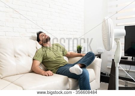 Hispanic Mid Adult Man Relaxing On Sofa In Front Of Fan In Living Room At Home