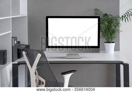Daylight interior with white modern mock-up computer monitor on an office table, orthopaedic chair, and greenery pot on a desk, copy space. Concept of home remotely working.