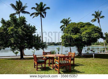Green Lawn In The Back Garden With Wooden Table And Chairs For Relaxing On Background Of Large Pond
