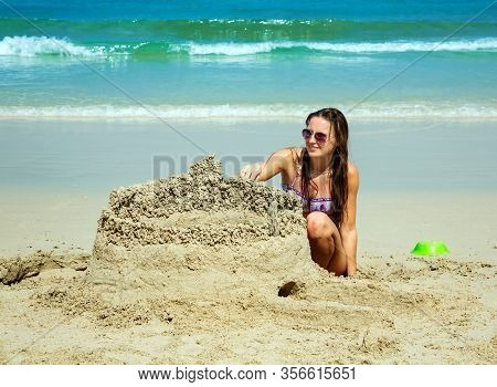 Young Woman Building A Sandcastle
