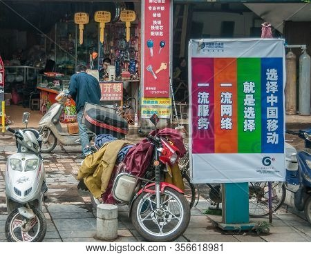 Guilin, China - May 10, 2010: Downtown. Motorbikes And Colorful Posters In Front Of Hardware Store W
