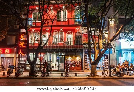 Guilin, China - May 10, 2010: Downtown. Night Shot Of Restaurant With Red Facade On Stret Scene With