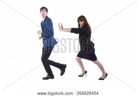 Businessman And Businesswoman Pushing Each Other Away.  Depicts Social Distancing Or Conflict Among