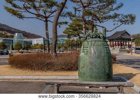 Jincheon, South Korea; March 12, 2020: Replica Of Larger Ceremonial Bell Sitting Behind A Park Bench