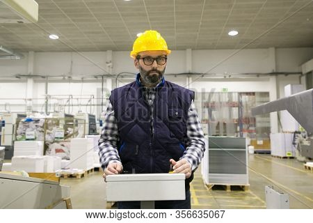 Serious Factory Machine Operator Pressing Buttons On Control Panel. Bearded Middle Aged Man In Hardh