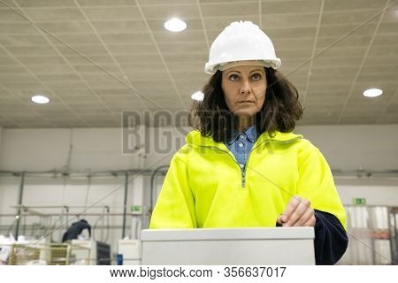 Focused Factory Worker Operating Production Process At Control Panel. Middle Aged Woman In Uniform A
