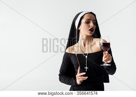Beautiful Sensual Nun Holding Glass Of Wine And Cigarette In Mouthpiece Isolated On Grey