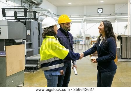 Smiling Factory Employees Shaking Hands With Office Manager. Cheerful Employees Communicating At Man