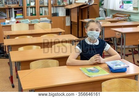Girl Schoolgirl In A Protective Medical Mask Sits Alone In A School Class. The Concept Of A Virus Ep