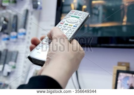 A Persons Hand Presses The Control Buttons Of The Tvs Black Remote Control At Their Leisure With A F
