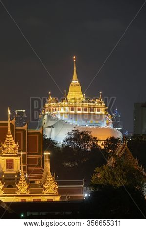 Golden Mountain Pagoda, A Buddhist Temple Or Wat Saket At Night In Bangkok Downtown Skyline, Urban C