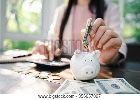 Closeup Of Business Woman Hand Putting Money Into Piggy Bank For Saving Money. Saving Money And Fina