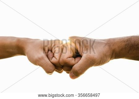 Closeup Young Man Fist Bump On The Sky Background. Friendship & Teamwork Concept.