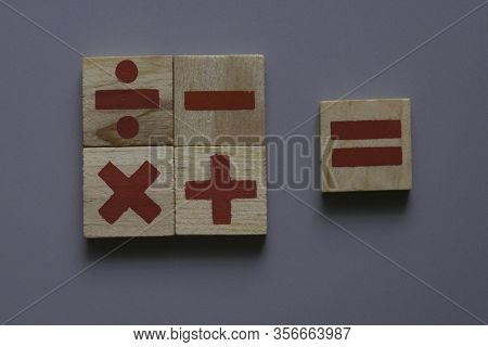 Top View Of Wooden Addition, Subtraction, Multiplication And Division. They Are Four Basic Operation