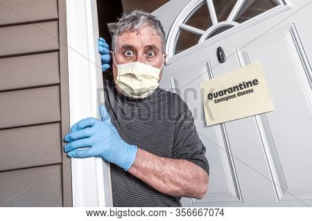 Man wearing mask and gloves afraid of virus exposure with quarantine sign that says