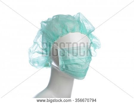 Surgical cap and mask on mannequin isolated on white background.