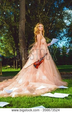 Beautiful fairy girl with the violin and sheet music on a sunny glade in the park. Musical concept. Classical music, violin.