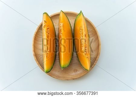 Fresh Melons Sliced On Wooden Plate On White Background