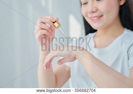 Smile Asian Woman Holding A Product Serum Bottle For Spa Products And Make Up. The Skin Is Smooth An