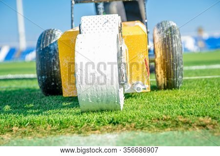 Splashing White Paint On The Grass To Help The Machine To Mark The Boundaries Of A Football Field.