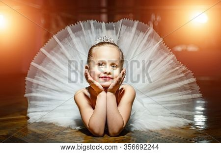 A Portrait Of Cute Smiling Ballerina In White Tutu And Crown Laying On The Wooden Floor With Face In