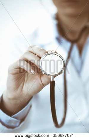 Unknown Doctor Woman Holds Stethoscope Head, Close-up. Physician Ready To Examine And Help Patient.