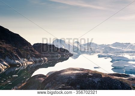 Big Icebergs In Ilulissat Icefjord At Sunset. Ilulissat Village, Western Greenland