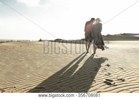 Back View Of Young Couple Strolling On Sandy Beach. Husband And Wife Strolling On Seashore During Va