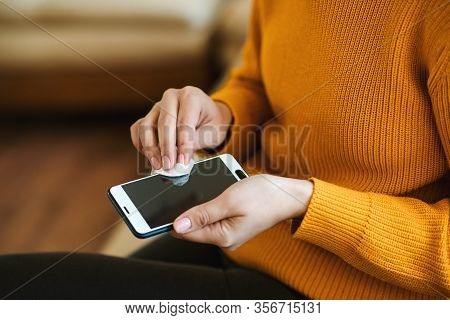 Woman Disinfecting Phone With Antiseptic Wet Wipe. Antiseptic Napkin To Prevent Spread Of Germs, Bac