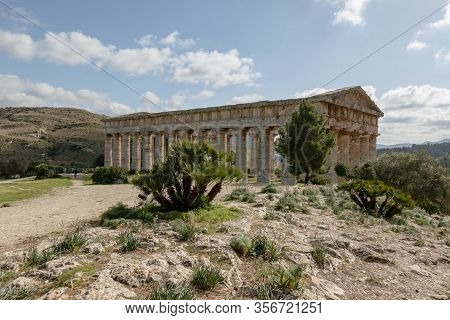 Ancient Doric Temple Of Segesta Hidden Behind The Trees And Rocks In Nice Sunny Spring Day