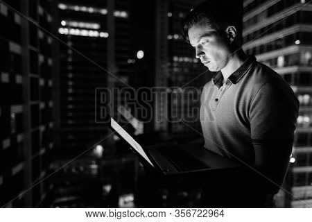 Young Handsome Man Using Laptop Against Glass Window With View Of The City At Night