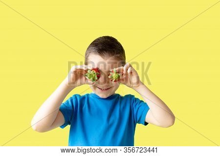 Smiling Boy Holds A Strawberry In Hands On Bright Yelow Background, Summer Holiday Concept