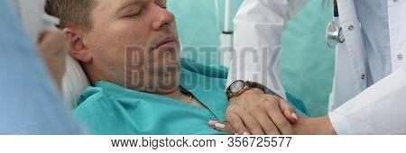 Portrait Of Hard Unhealthy Patient In Emergency Medicine. Professional Resuscitator Making Resuscita