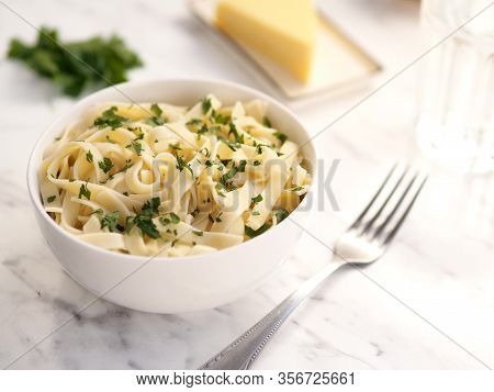 Italian Pasta In A White Bowl With Fork Parsley And Cheese Around. Fettuccini Pasta With Cheese Crea