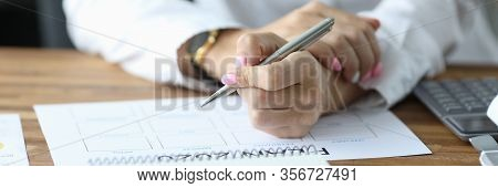 Close-up View Of Womans Hands Filling Paper With Months. Person Sitting In Office With Silver Pen An