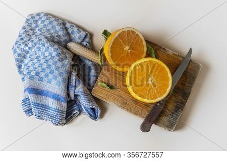 Orange Cut In Half, On A Cutting Board, Next To A Blue Dishcloth, On A White Background