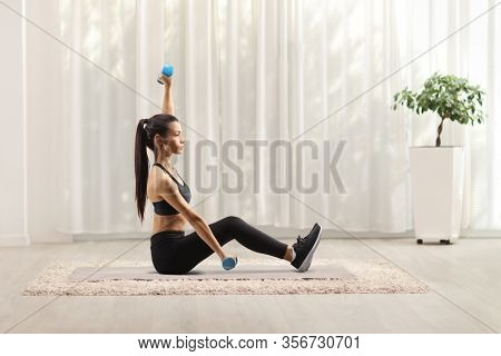 Young woman exercising with dumbbells on a mat at home