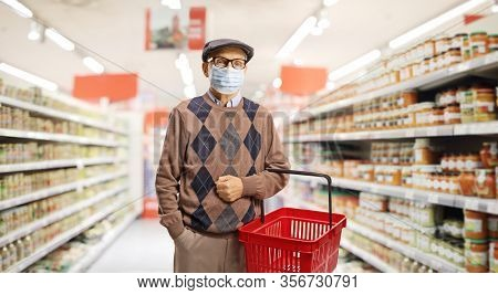 Senior man shopping in a supermarket with a medical face mask