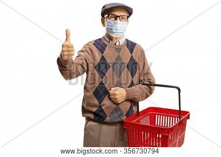 Elderly man with a protective face mask showing thumbs up and carrying a shopping basket isolated on white background