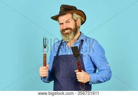 Bbq Food. Tools Roasting Meat. Man In Apron Hold Barbecue Grill. Hipster Dyed Beard Promoting Bbq Eq