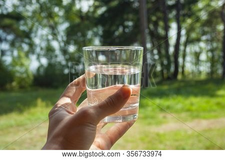 Water Glass At Mans Hand On Sunbeams. Hydration At Hot Summer Days Concept. Healthy Lifestyle Symbol