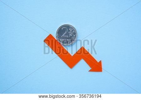 Two Rouble Coin On Blue Background With Red Arrow Down. Exchange Rate Chart. Ruble Depreciation. Exc